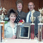 Kathy Frombach and her parents display her medals and trophies.