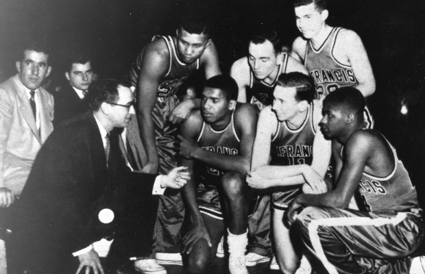 Hall of Famers Skip Hughes, left, and Maurice Stokes, center are part of a St Francis team huddle