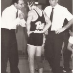 Pat Pecora discusses strategy with UPJ wrestler Larry Hohman, as assistant coach Rob Yahner listens, left to right.