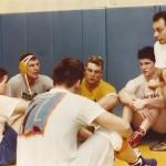 Pat Pecora, right, addresses his squad in the original UPJ wrestling room at the Sports Center.
